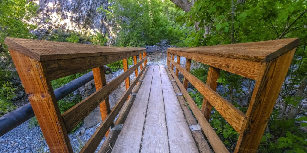 Bridge with rails on a rocky terrain in Provo. Narrow wooden bridge with rails on a hiking trail in Provo Canyon, Utah. The bridge leads to a rocky and rugged terrain with trees and lush foliage.