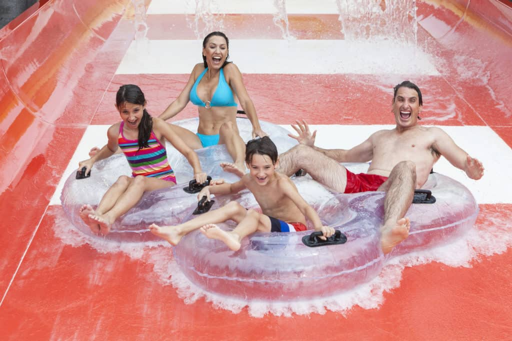 A happy family of mother, father and children, son and daughter, having fun on vacation on a slide at a waterpark